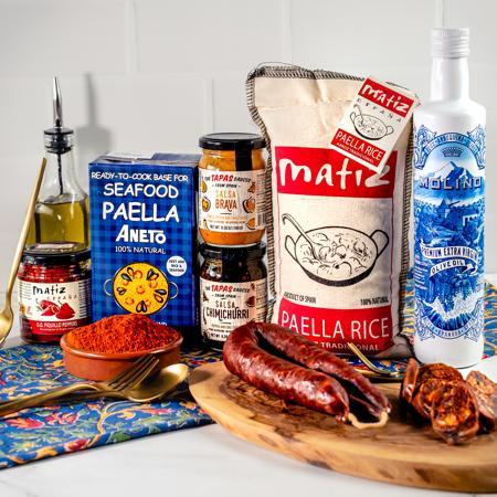 Spanish Pantry and Paella Kit featuring Matiz Paella Rice and Paella Broth, Tapas Chimichurri and  Bravas sauces and Palacios Dry Chorizo.